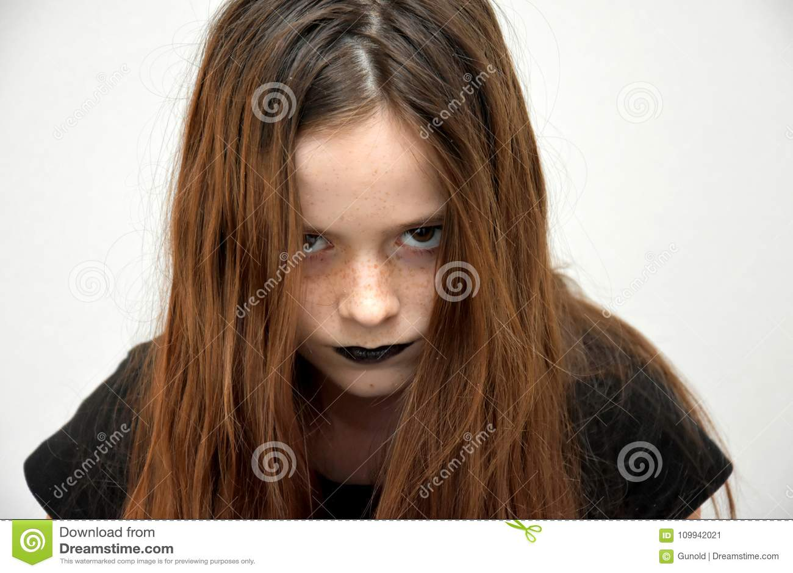 Tonårs- flicka i gotisk stil som ser mycket ilsken