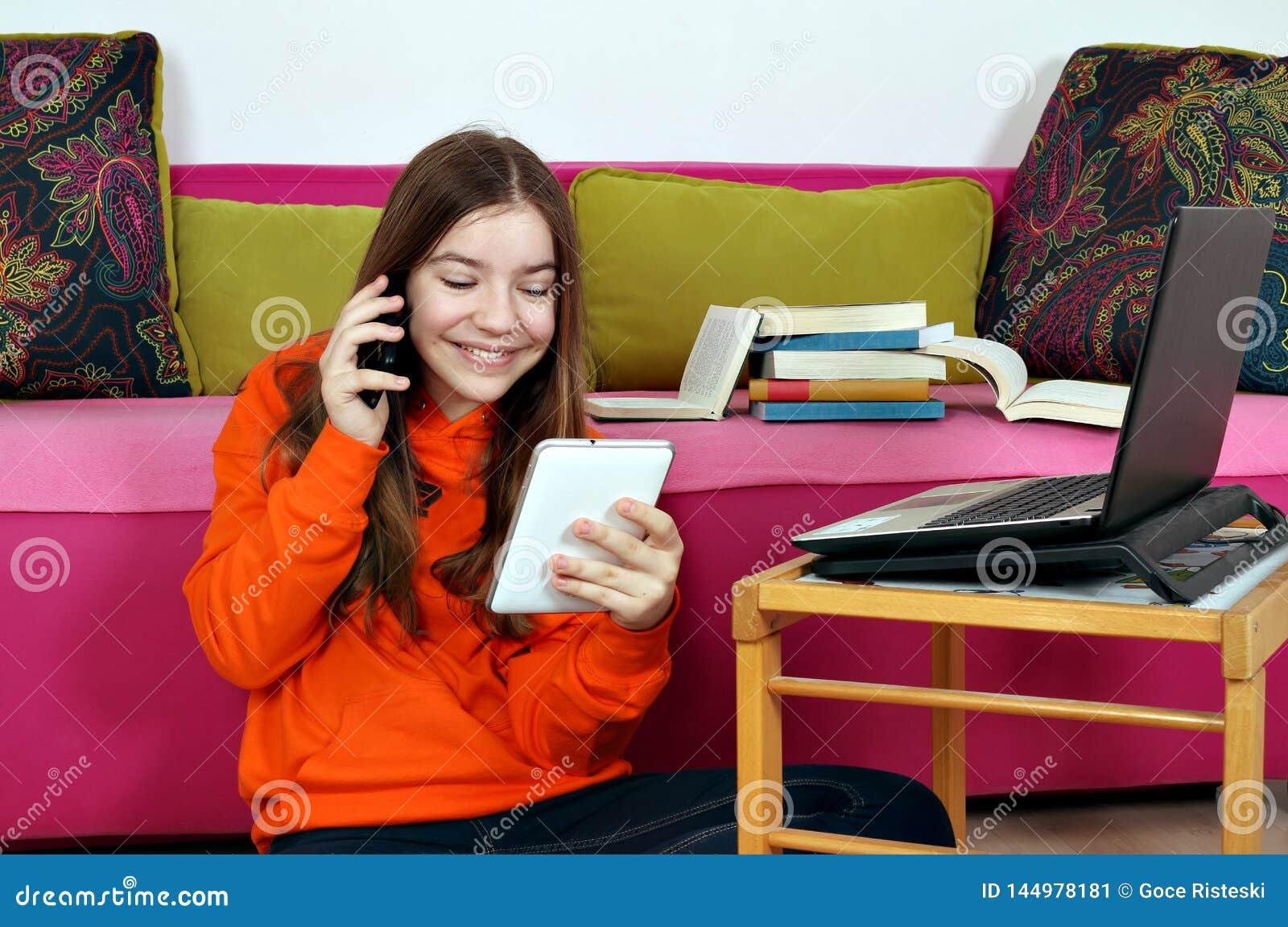 Tonårs- flicka med den smartphoneminnestavlan och bärbara datorn