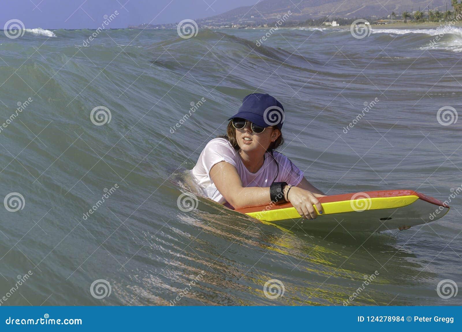 Tonårs- flicka på röd och gul bodyboard