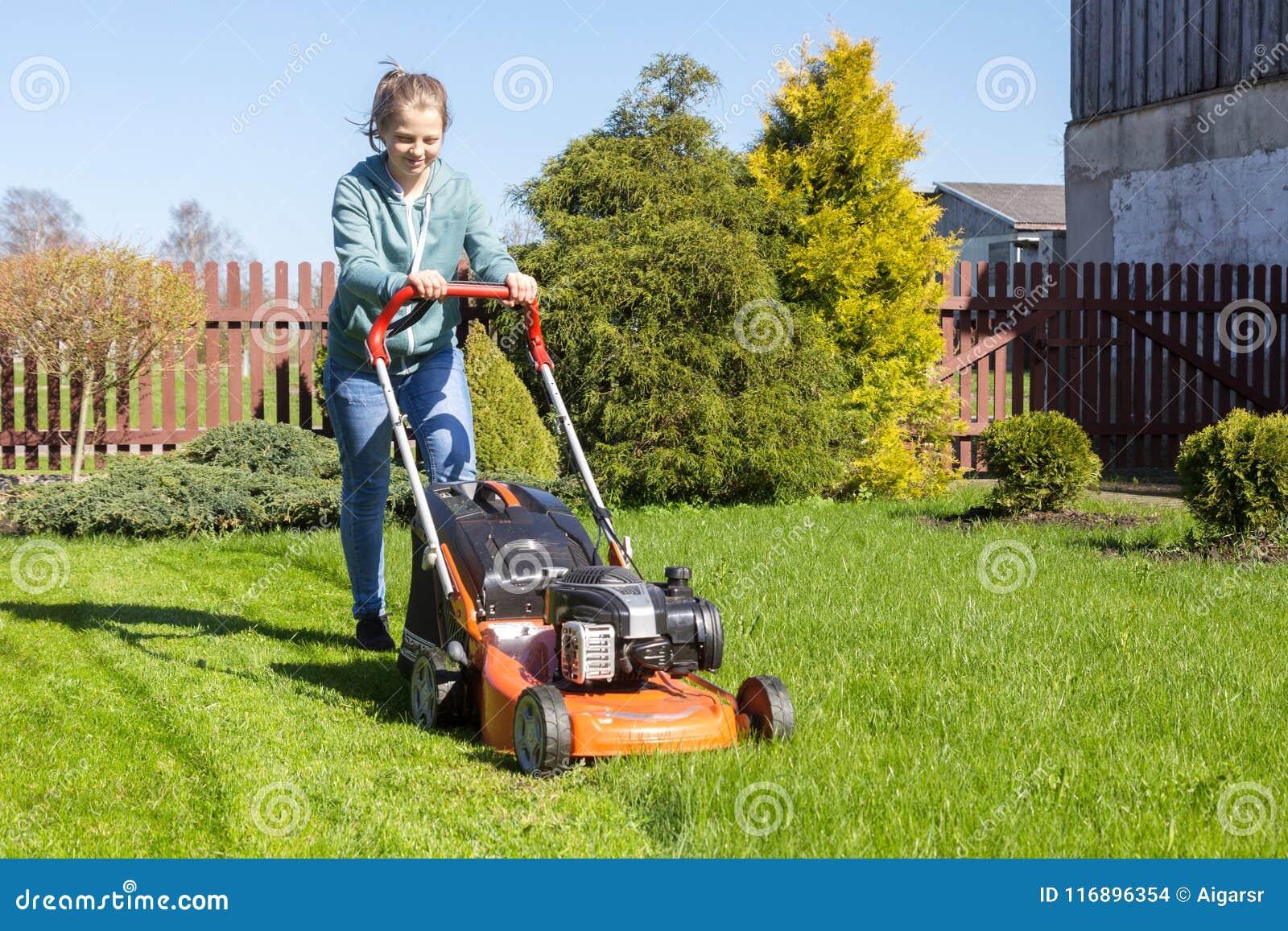 Tonårs- flicka som mejar gräs