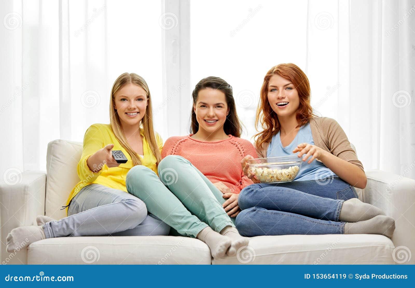 Tonårs- flickor eller vänner som hemma håller ögonen på tv