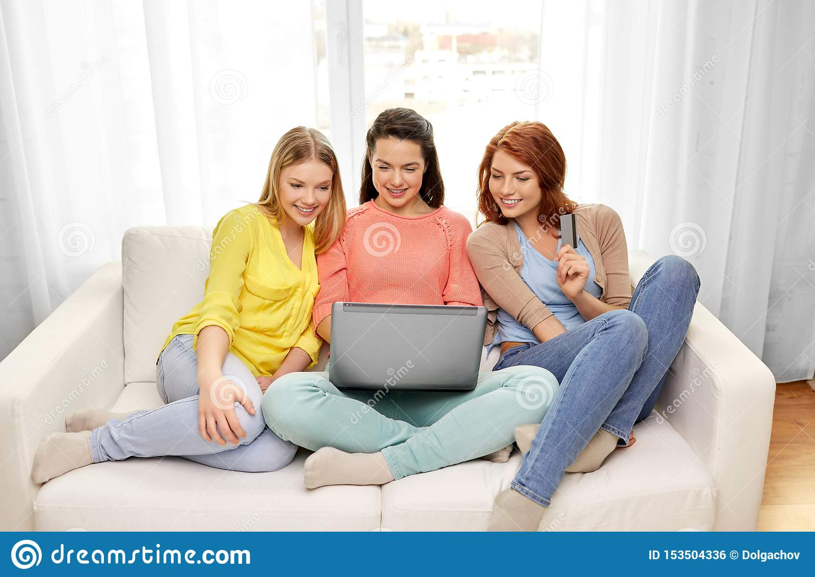 Tonårs- flickor med bärbara datorn och kreditkorten