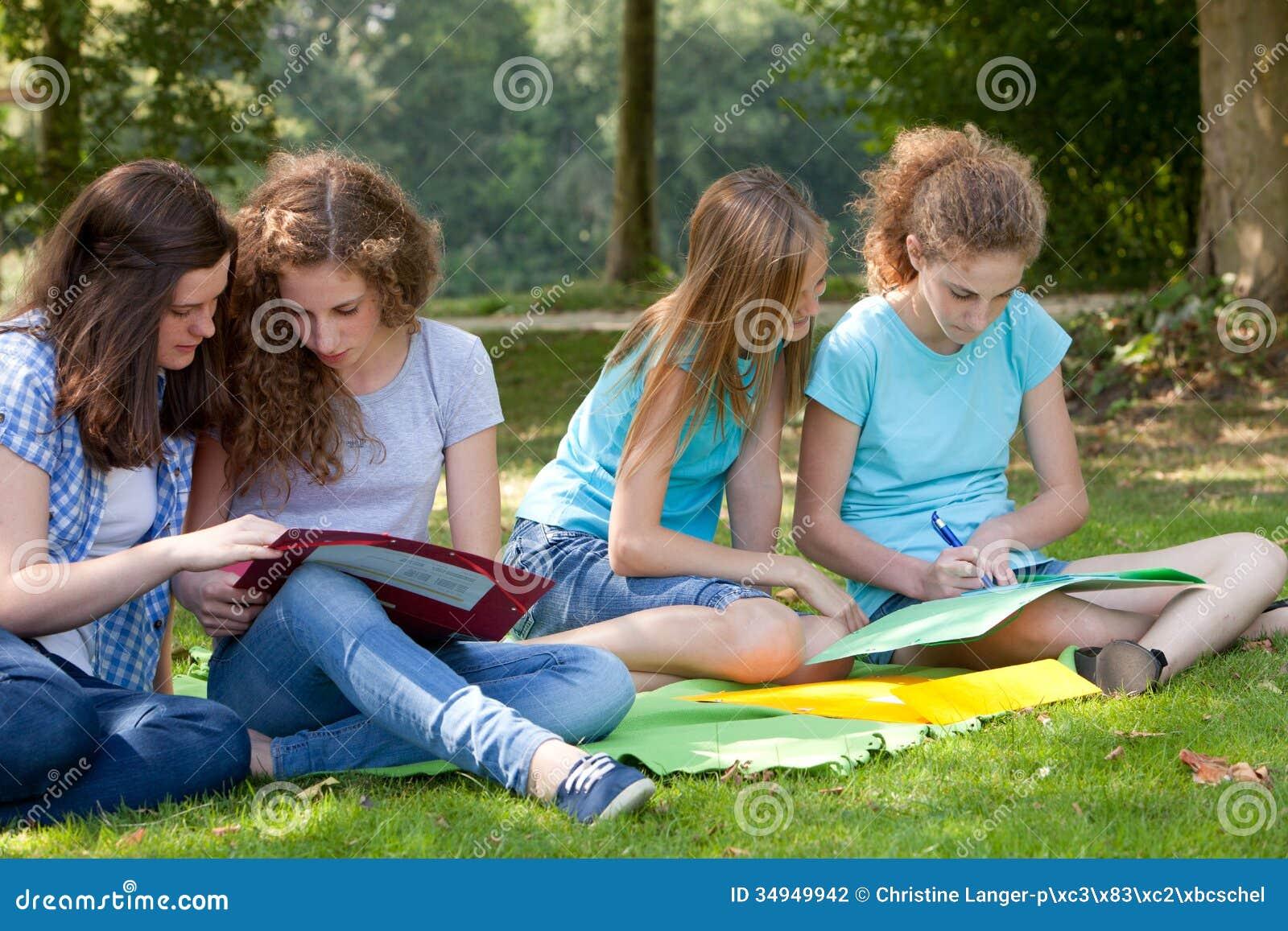 Tonårs- flickor som tillsammans studerar i parkera