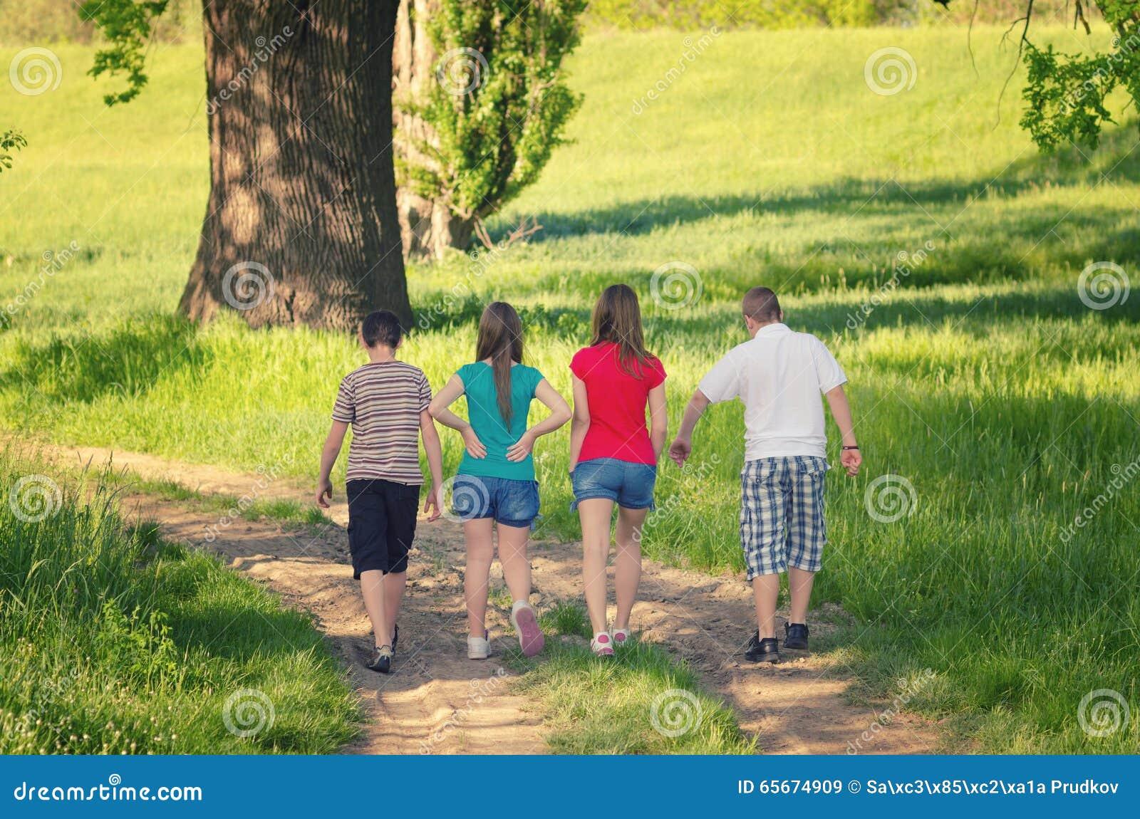 Tonårs- pojkar och flickor som går i natur på solig vårdag