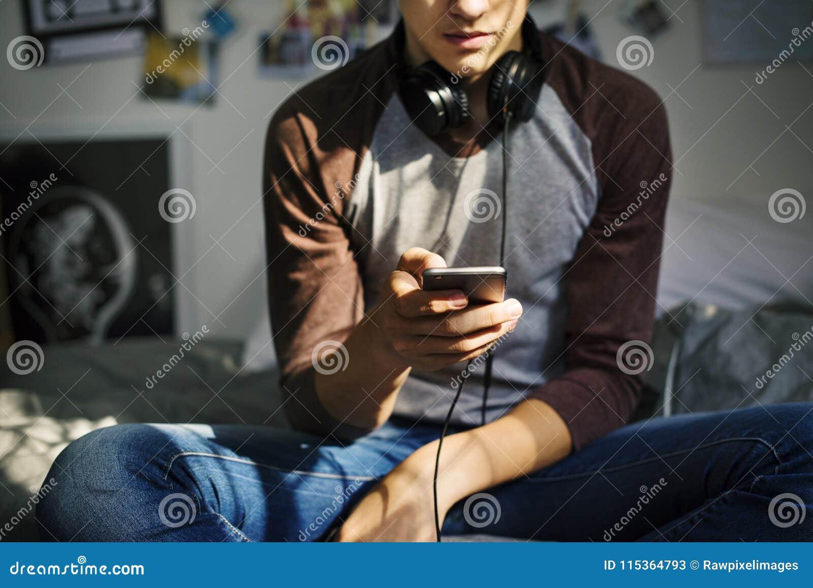 Tonårs- pojke i ett sovrum som lyssnar till musik till och med hans smartphone