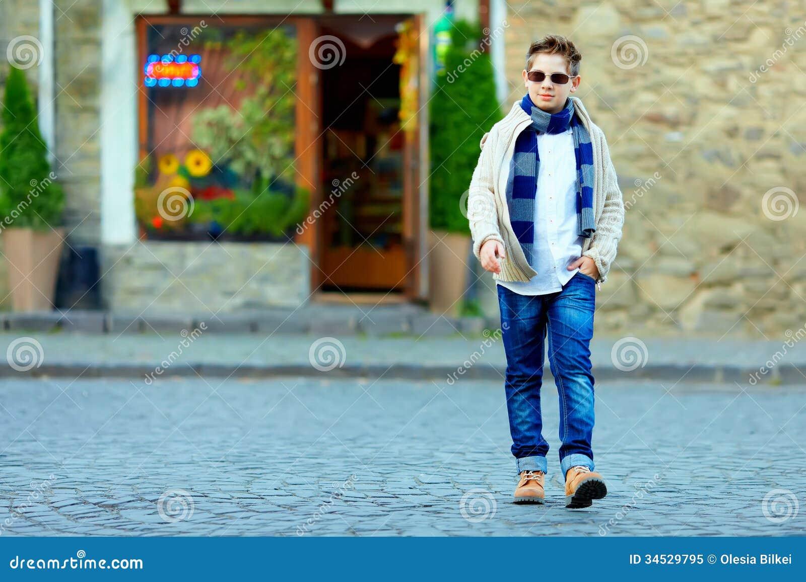 Tonårs- pojke som korsar gatan av den gamla staden