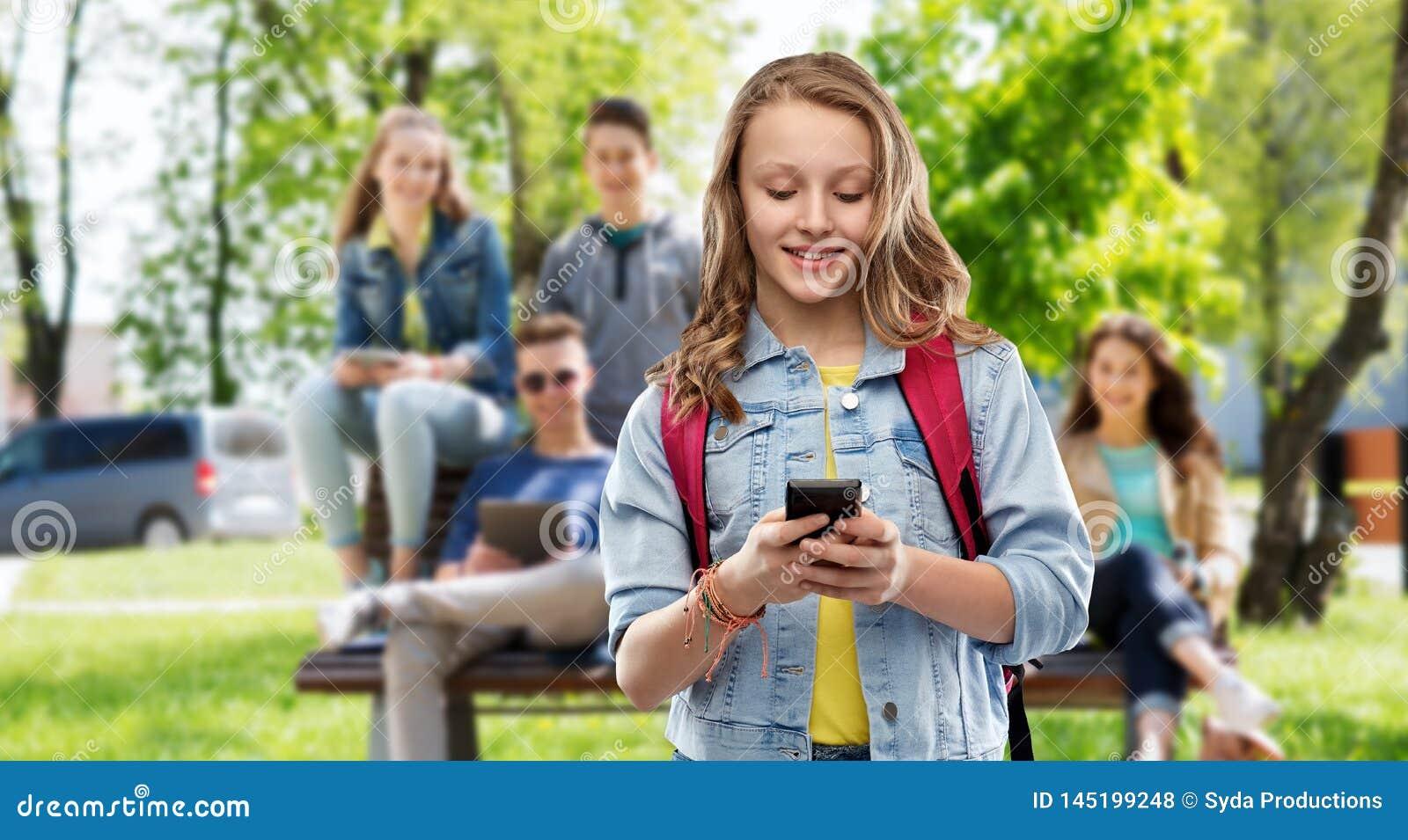 Ton?rig studentflicka med skolap?sen och smartphonen