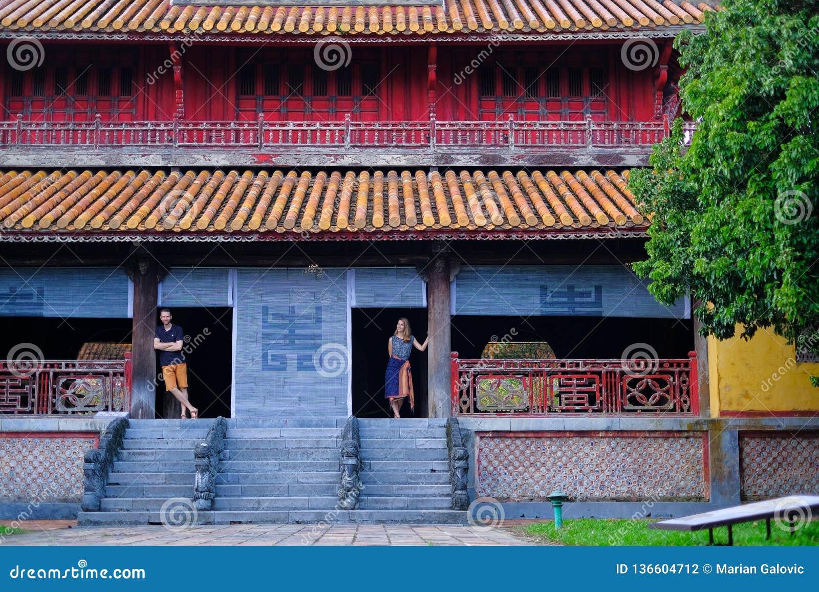 Ton/Vietnam, 17/11/2017: Par som står inom ett traditionellt hus med det dekorativa belade med tegel taket i citadellen av tonen,