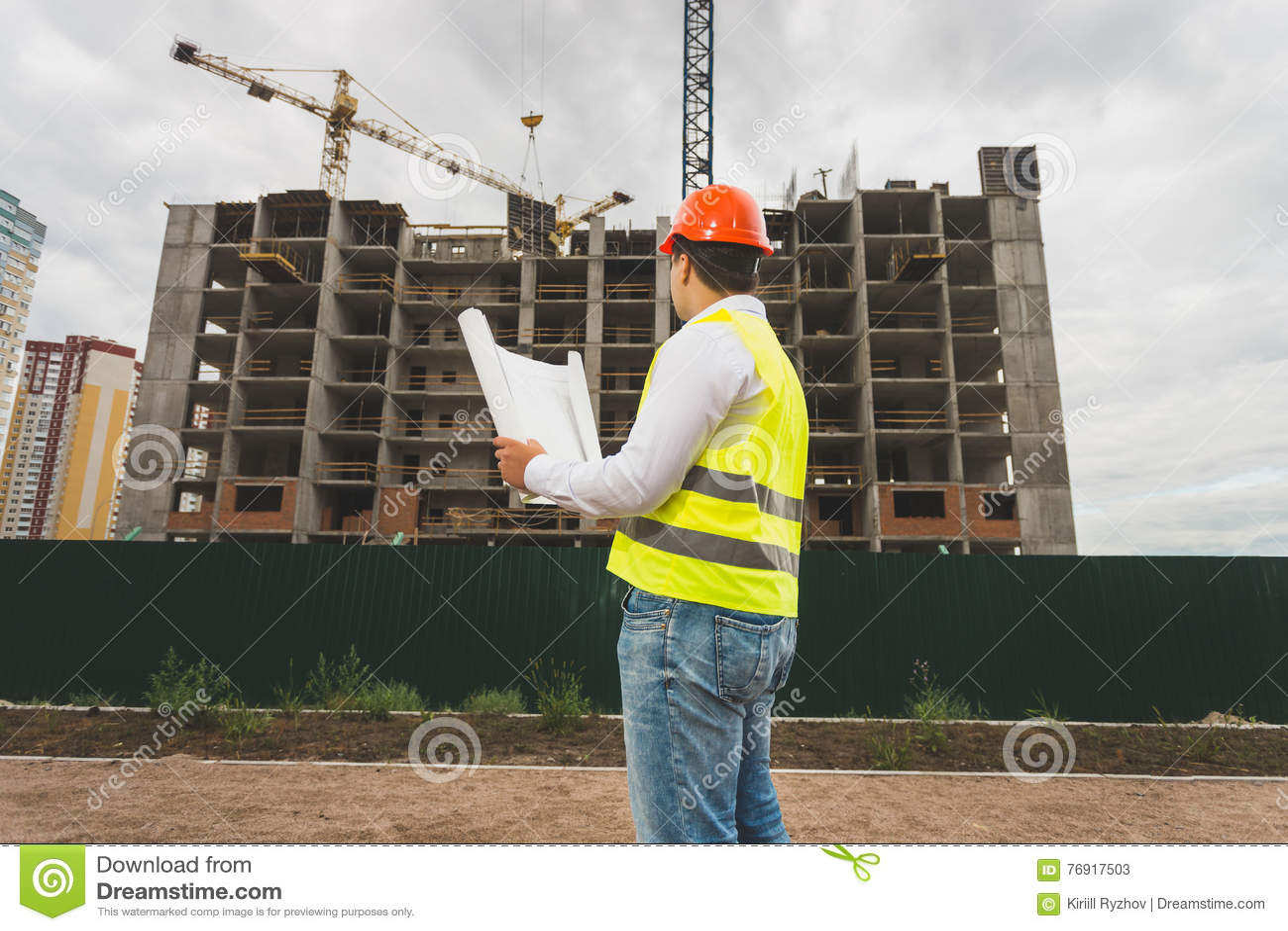 Tonad bild av teknikern i hardhaten som kontrollerar byggnadsplatsen