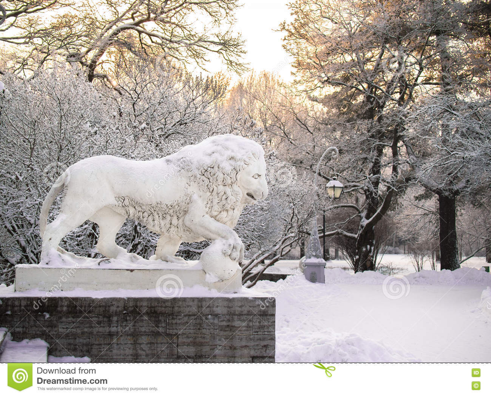 Tonad bildskulptur av ett lejonanseende på en sockel i vintern i St Petersburg mot bakgrunden av dettäckte trädet