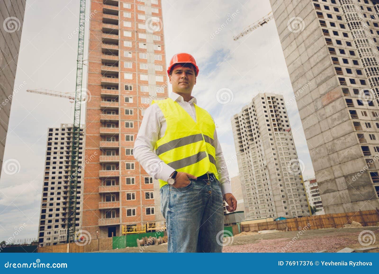 Tonad stående av teknikern som poserar mot byggnader under constr