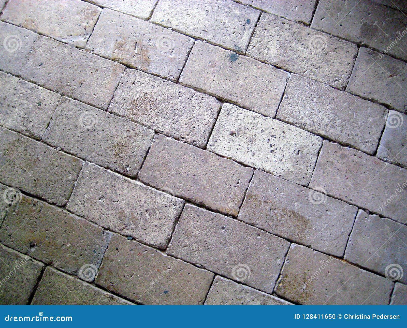 Tonalità rosse giallo-chiaro del bello vecchio pavimento del mattone