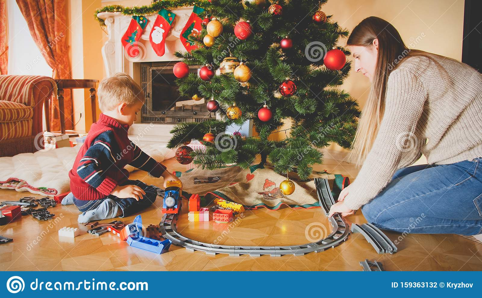 Toned Photo Of Family Playing With Toy Railroad On Floor At Living Room On Christmas Morning ...