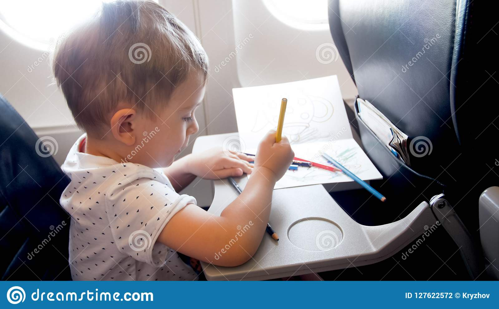 Toned portrait of little boy traveling by plane and drawing with pencils during long flight