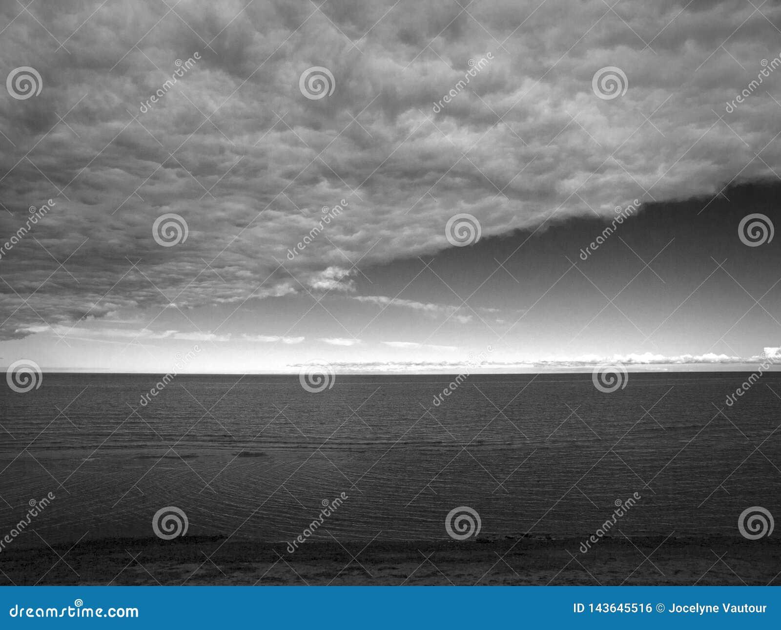 Toneel oceaanmening met bewolkte hemel in zwart-wit