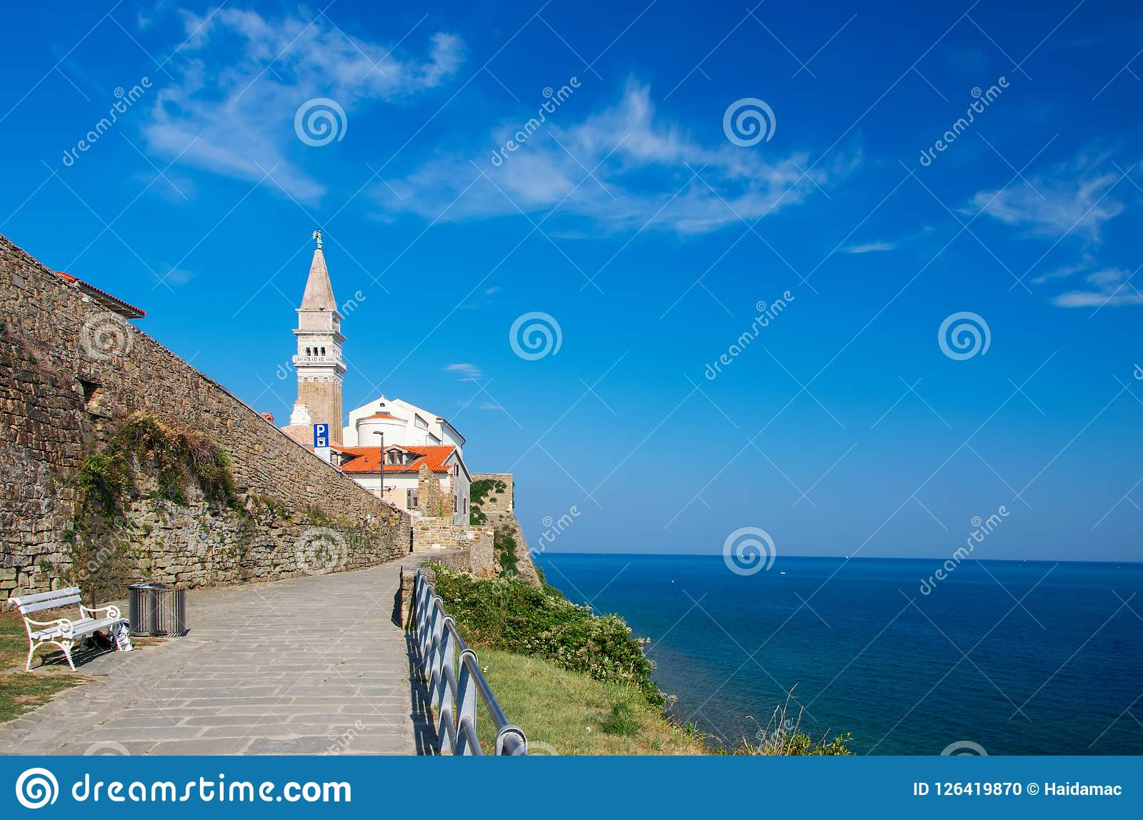 Toneelmening van kustlijn van Adriatische overzees met steeg langs oude de stadsmuren van Piran en kathedraal op achtergrond, Slo Stock Foto