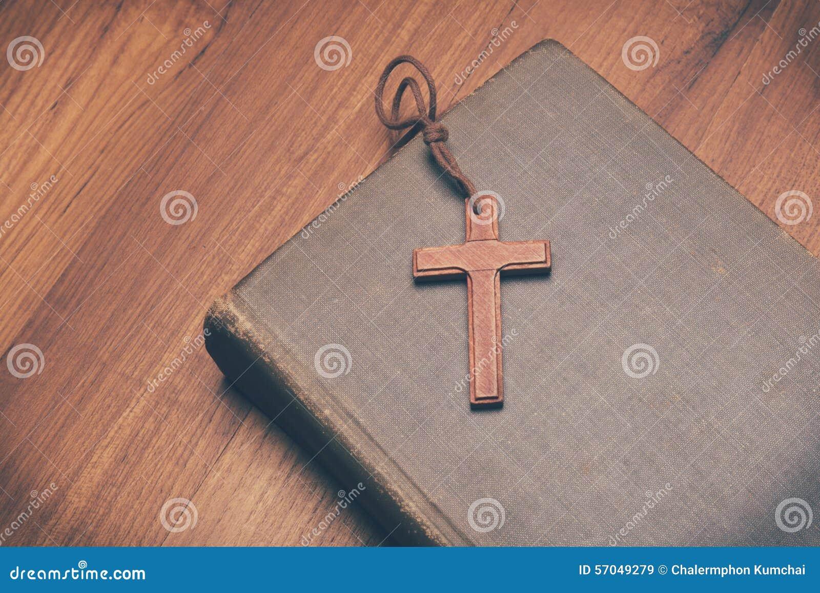 Tono del vintage del collar cruzado cristiano de madera en la Sagrada Biblia