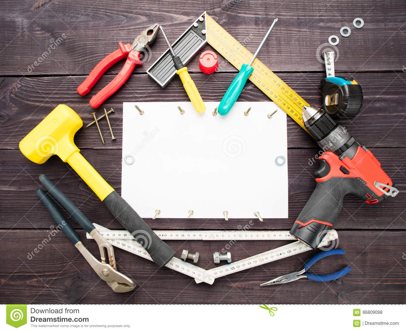 The tool building on the wooden background around the white sheet of paper