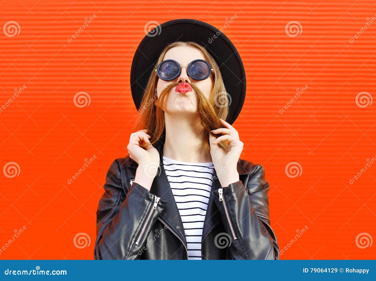 Toont de manier grappige vrouw die pret hebben snorhaar over kleurrijk rood
