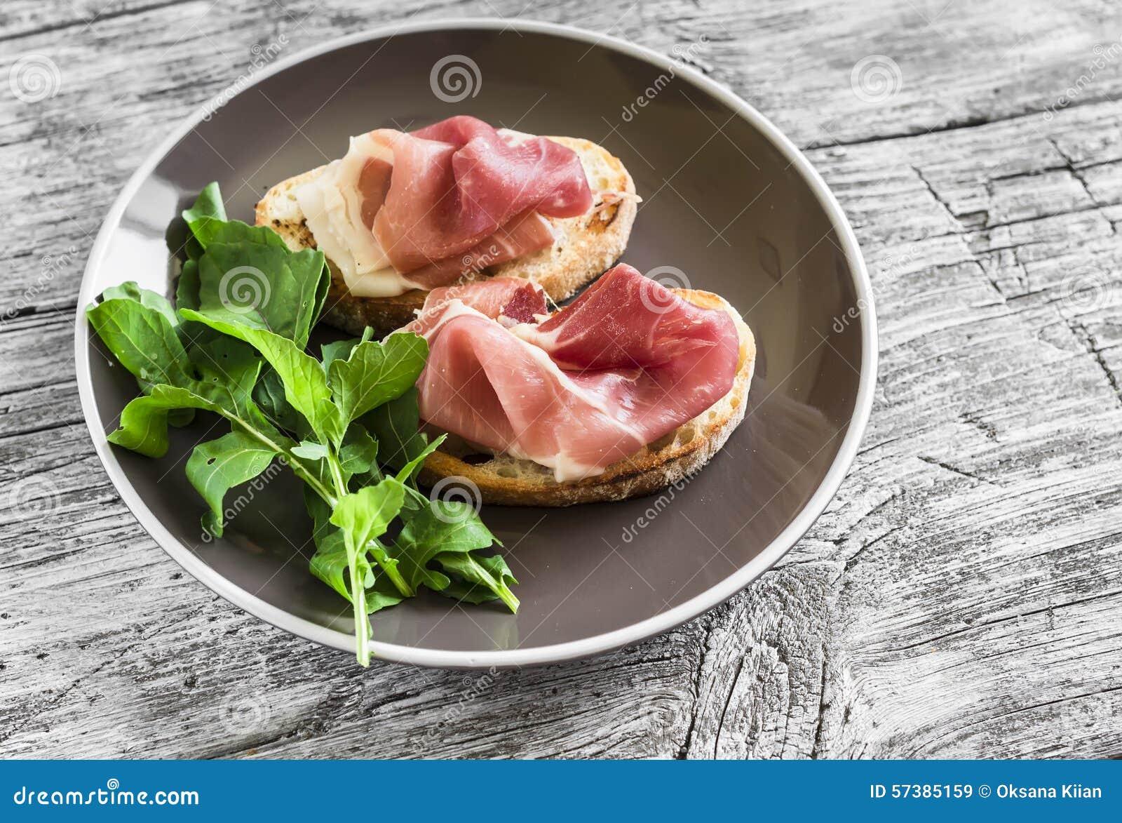 Toost met ham en verse arugula op een bruine plaat