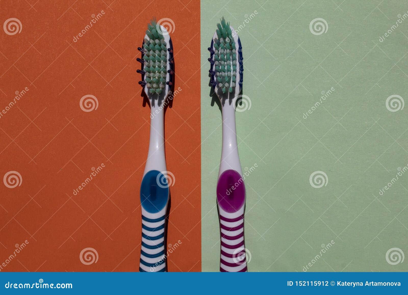 2 toothbrushes, błękit i menchii, Odizolowywający na zielonym i pomarańczowym tle