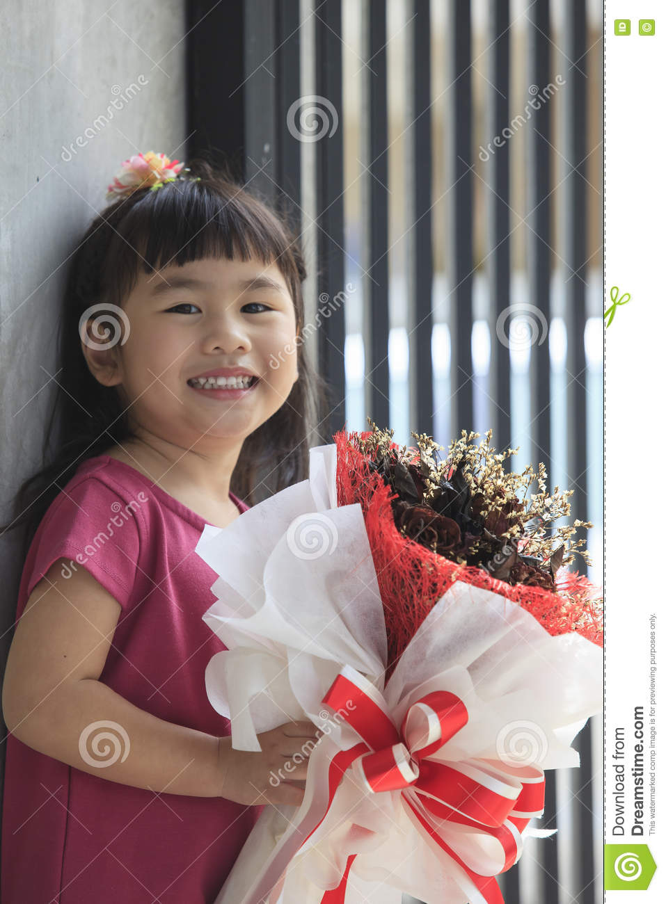 Toothy smiling face of asian kid happiness emotion and dry flowe royalty free stock photo izmirmasajfo