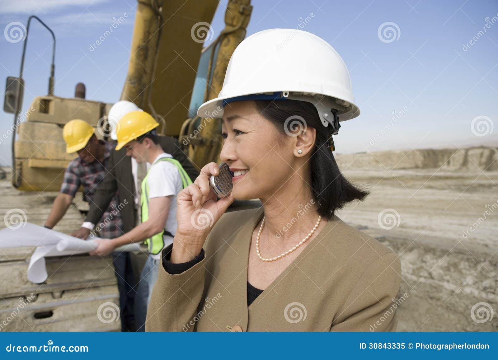 Topógrafo en el casco de protección en Front Of Workers Using Cellphone en sitio