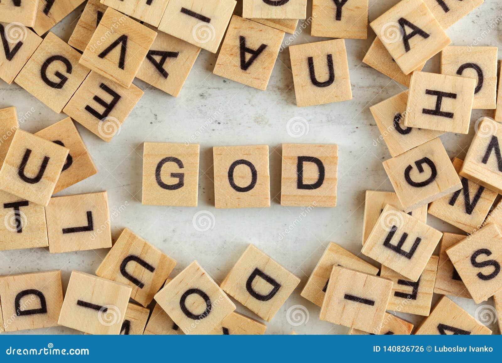 Top abajo de la visión, pila de bloques de madera cuadrados con DIOS de las letras en el tablero blanco