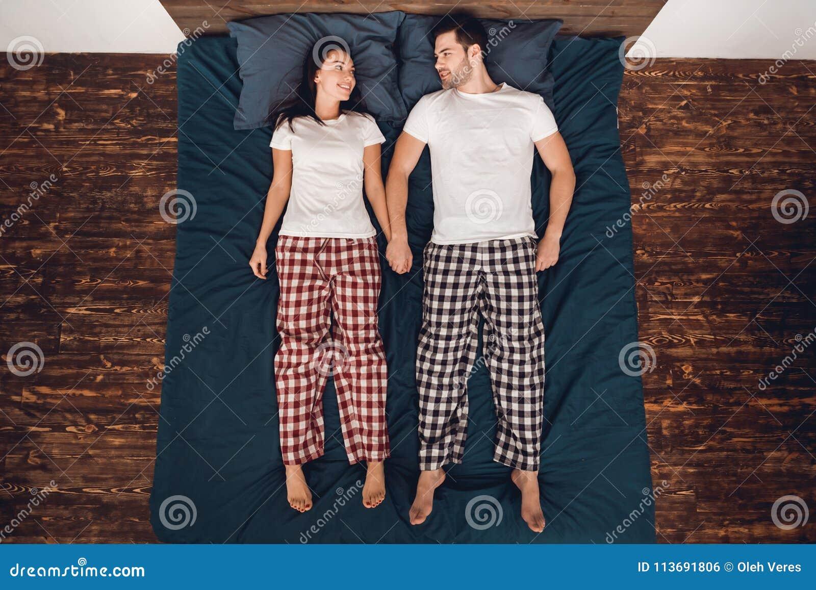Top beskådar Stilig man och härlig kvinna i pajamalögnraksträcka på säng och blick på de