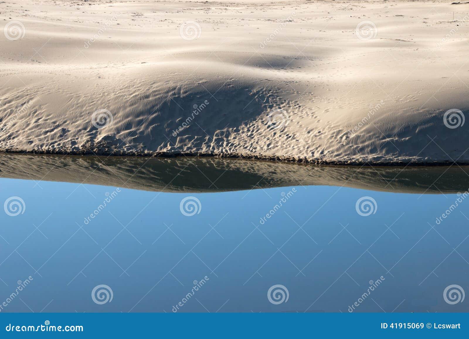 Top del banco reflejado en agua azul tranquila de la laguna