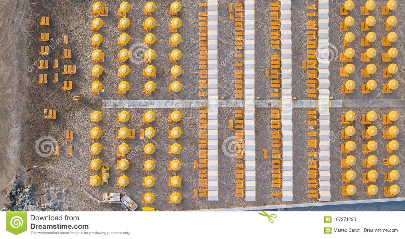 Top down drone aerial view of the umbrellas and gazebos on Italian sandy beaches. Riccione, Italy. Adriatic coast