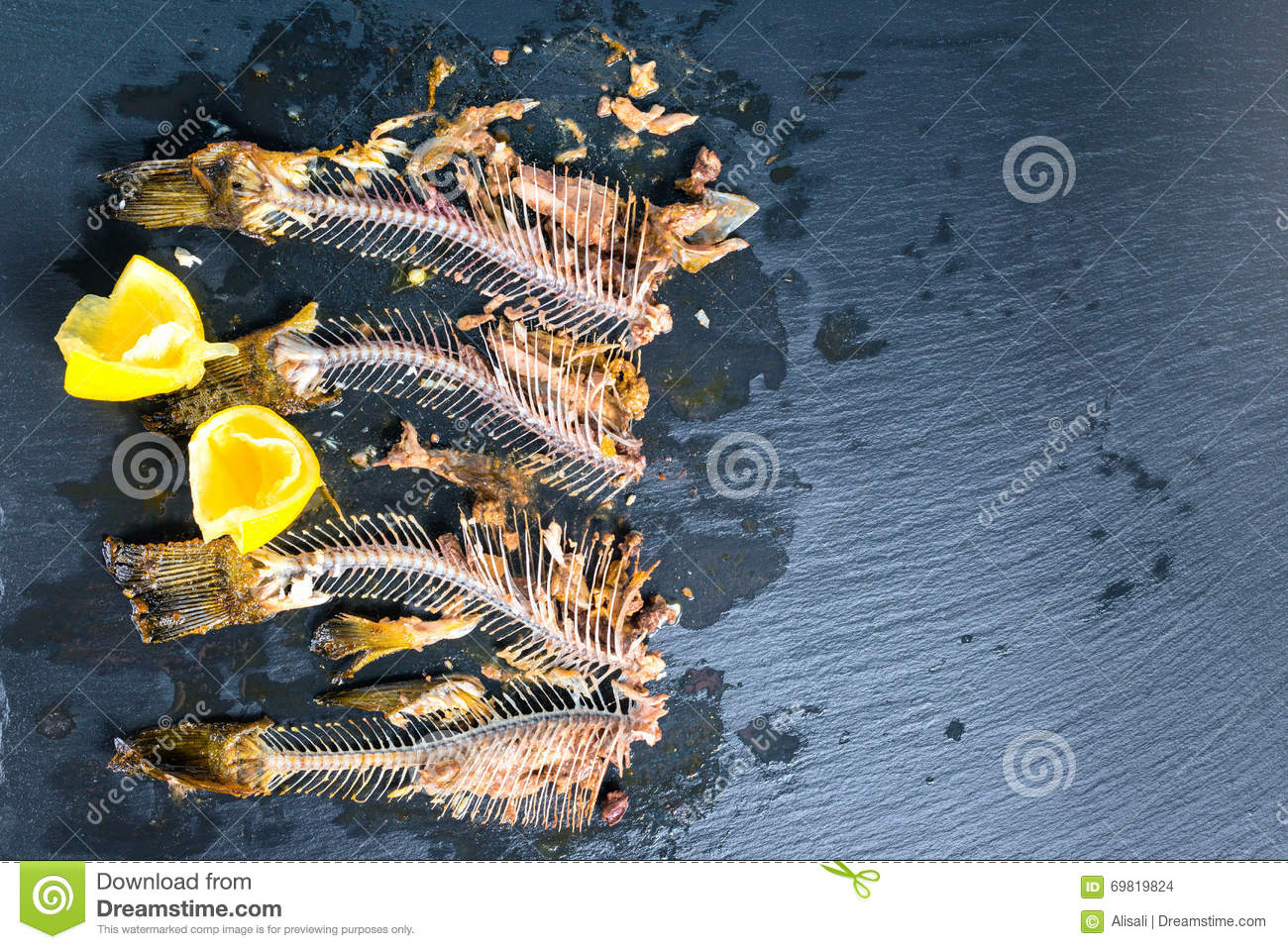 Top down of fish skeleton bones without heads, squeezed lemon on