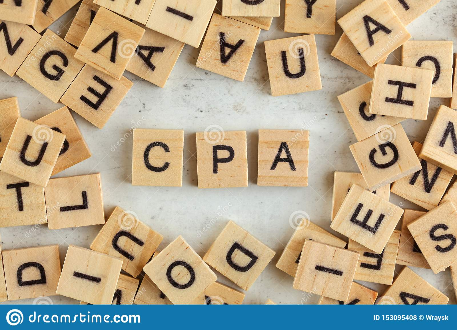 Top down view, pile of square wooden blocks with letters CPA stands for Cost per Action / Acquisition on white board