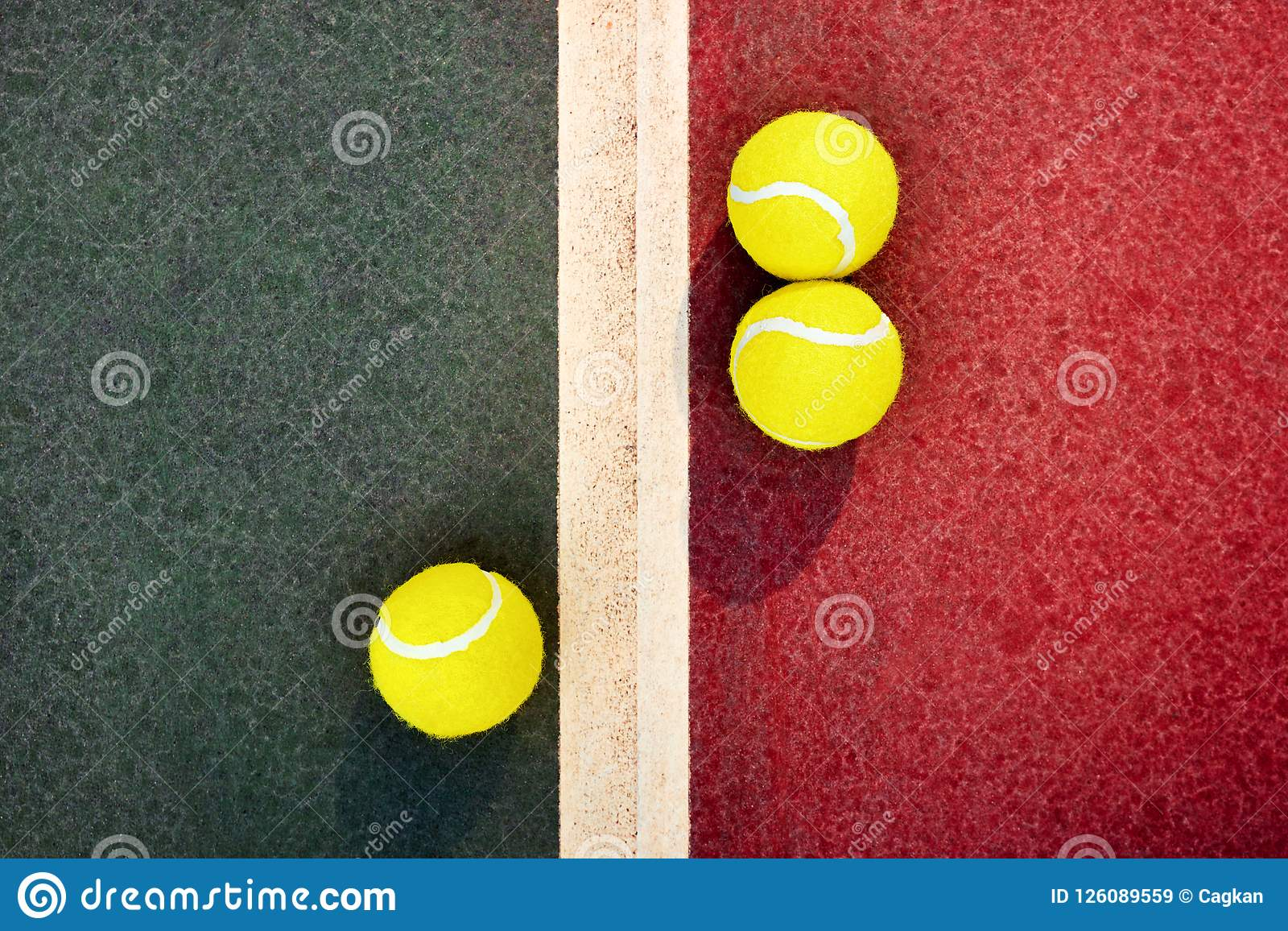 Three Yellow Tennis Balls Near The Line Of A Green Red Concrete