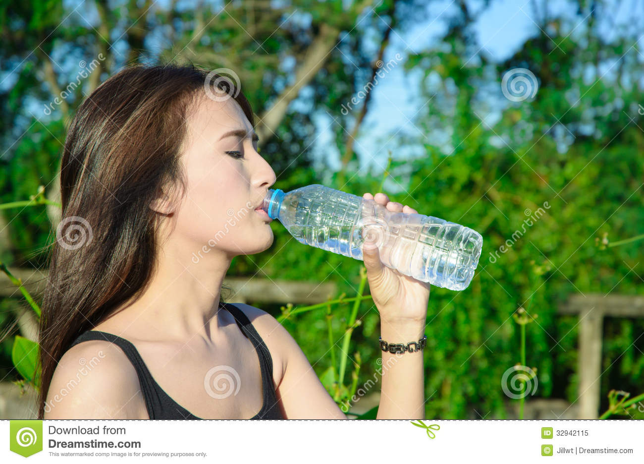 Top length asia young girl drink water from plastic bottle on natural ...