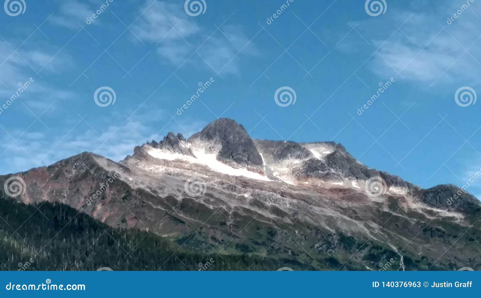Top nevado de la montaña debajo de un cielo azul con las nubes wispy