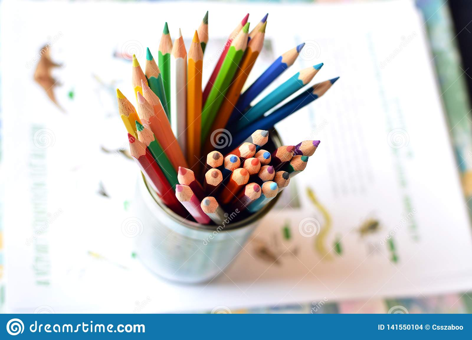 Top shot, close up of different, used, blunt, dull and sharpened colored pencils on bright papers background, space for text,