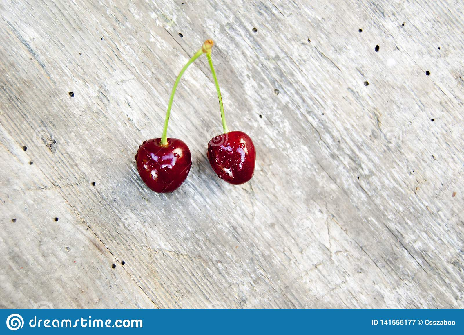 Top shot, close up of fresh sweet cherry with water drops on light rustic wooden table background, selective focus, space for