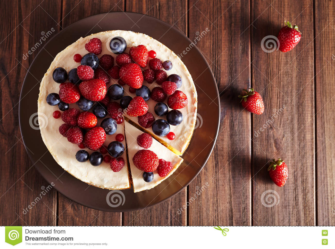 Top viev. Delicious Homemade creamy mascarpone New York Cheesecake with berries on dark wooden table. Close up.