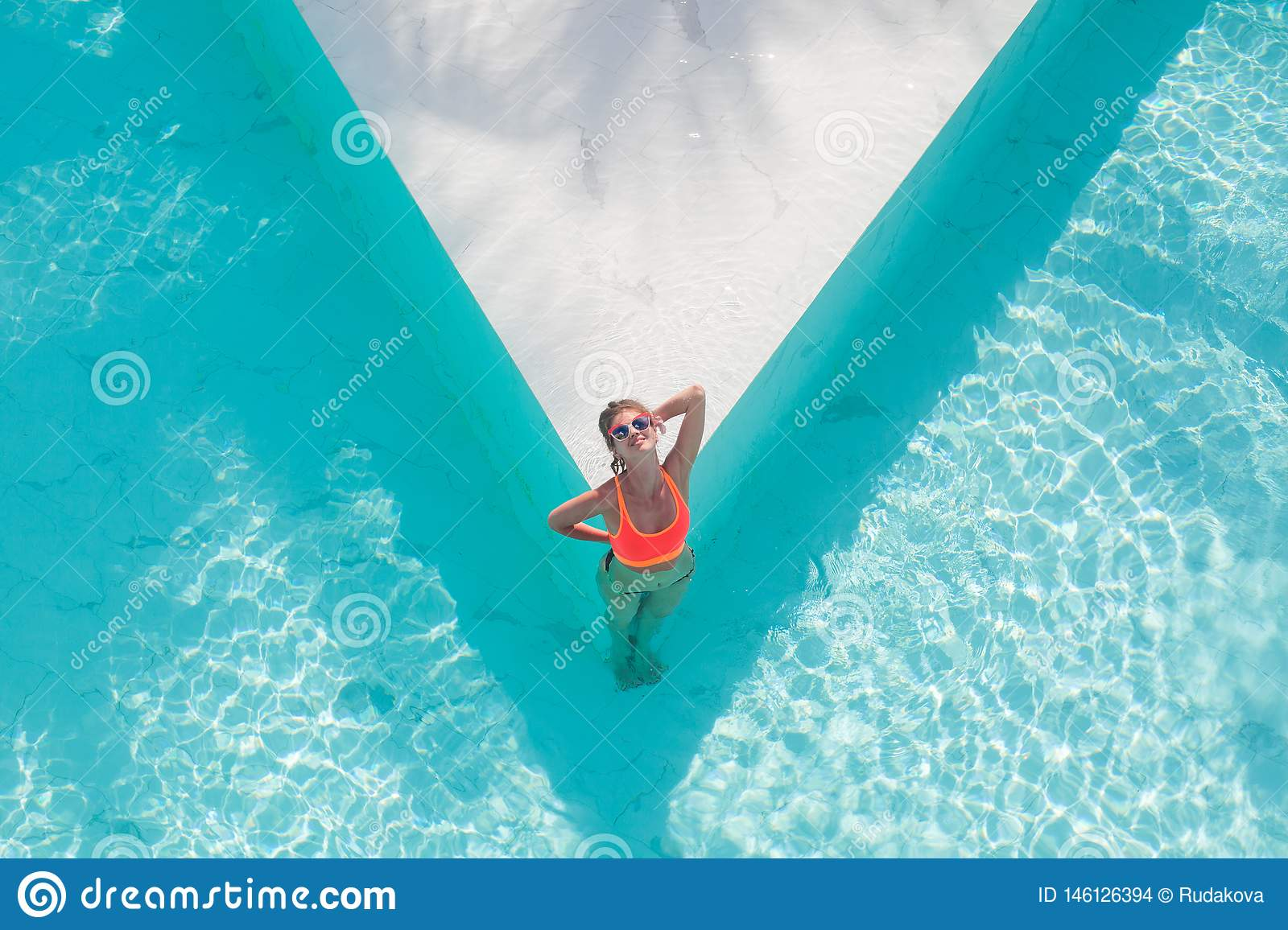 Top view aerial photo of model in bright swimwear relaxing in hotel pool during her summer weekend