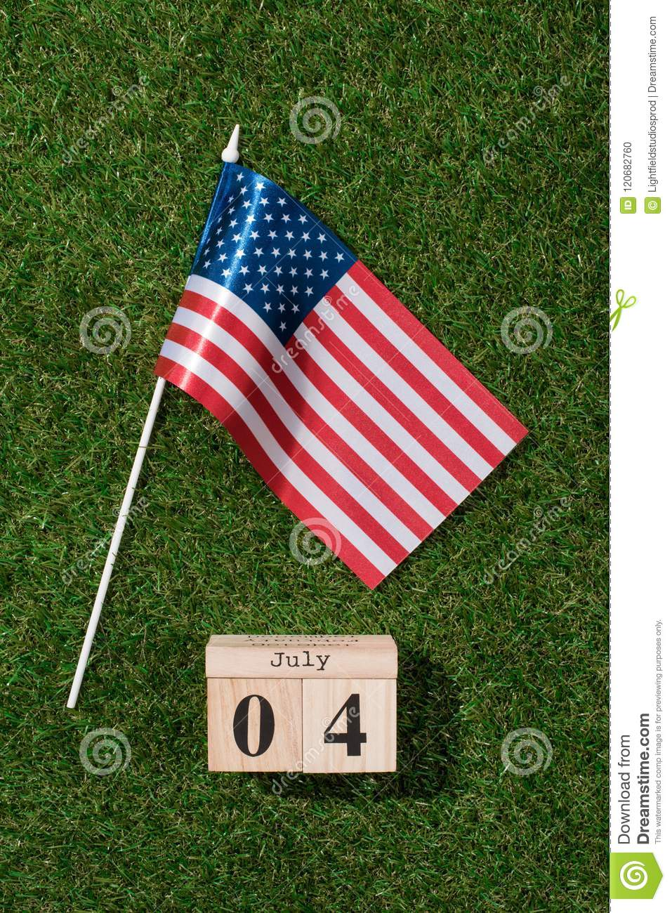 top view of american flagpole and wooden calendar with 4th july date on green grass, americas independence
