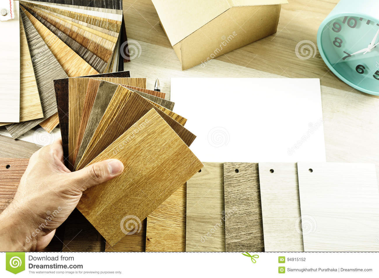 Top view of Architects & Interior designers hands design to choose wood floor materials on table in workplace in the morning.