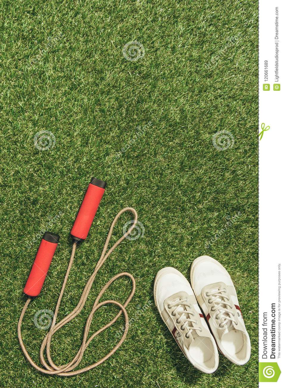 top view of arranged sneakers and skipping rope