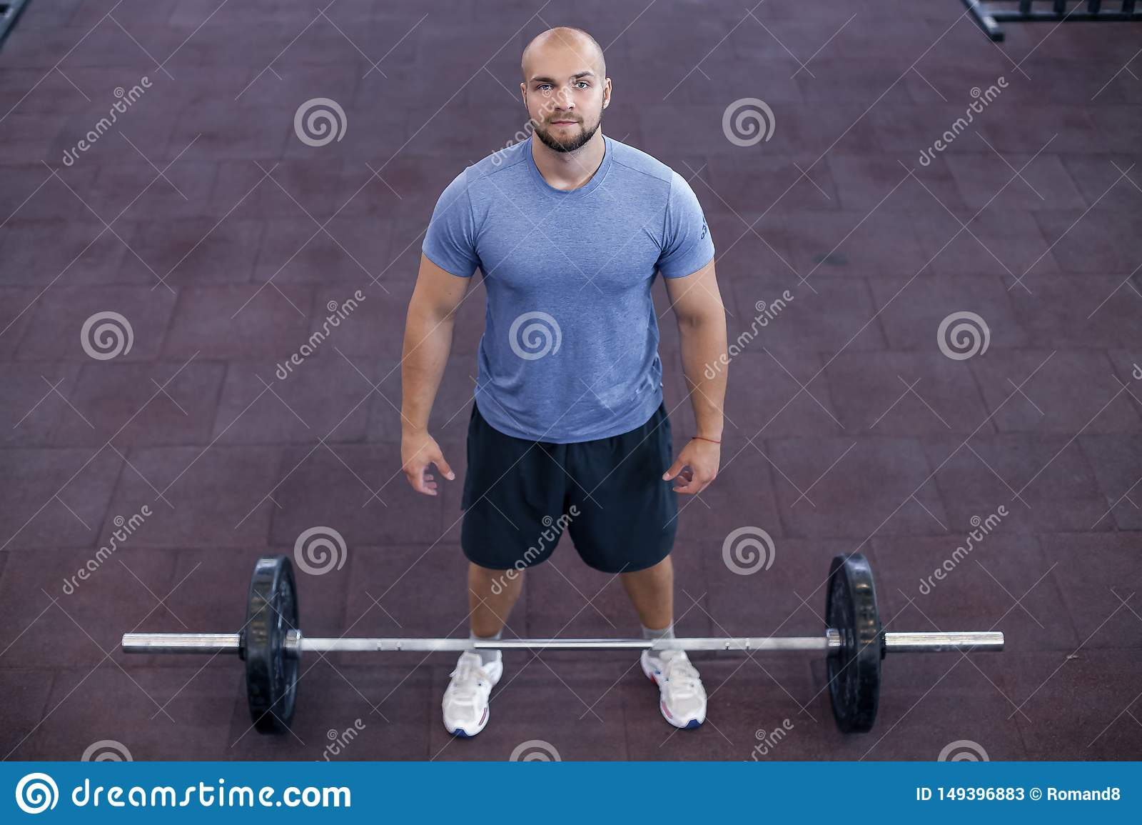 Top view of a athletic man works out at the gym with a barbell
