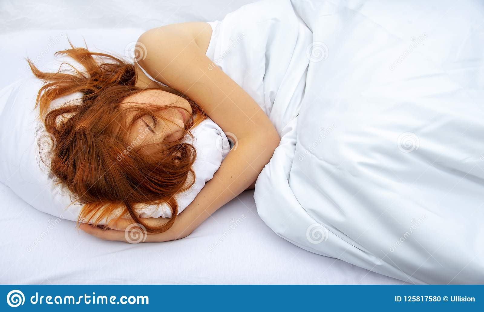 Top view of attractive, young, red-haired woman relaxing in bed hugging a soft white pillow, sleeping