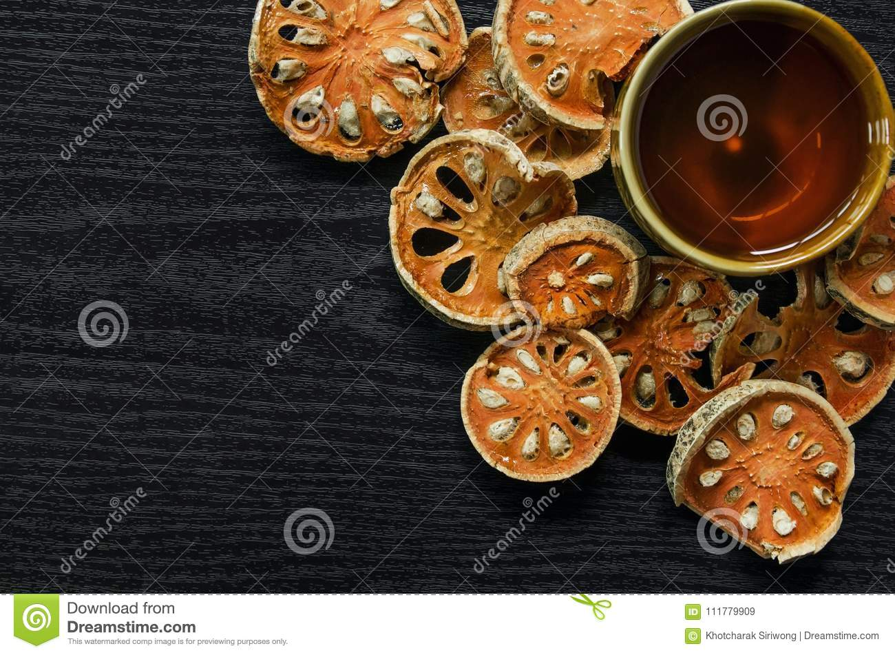 Top view of bael dry and glass tea and bael juice on the wooden floor