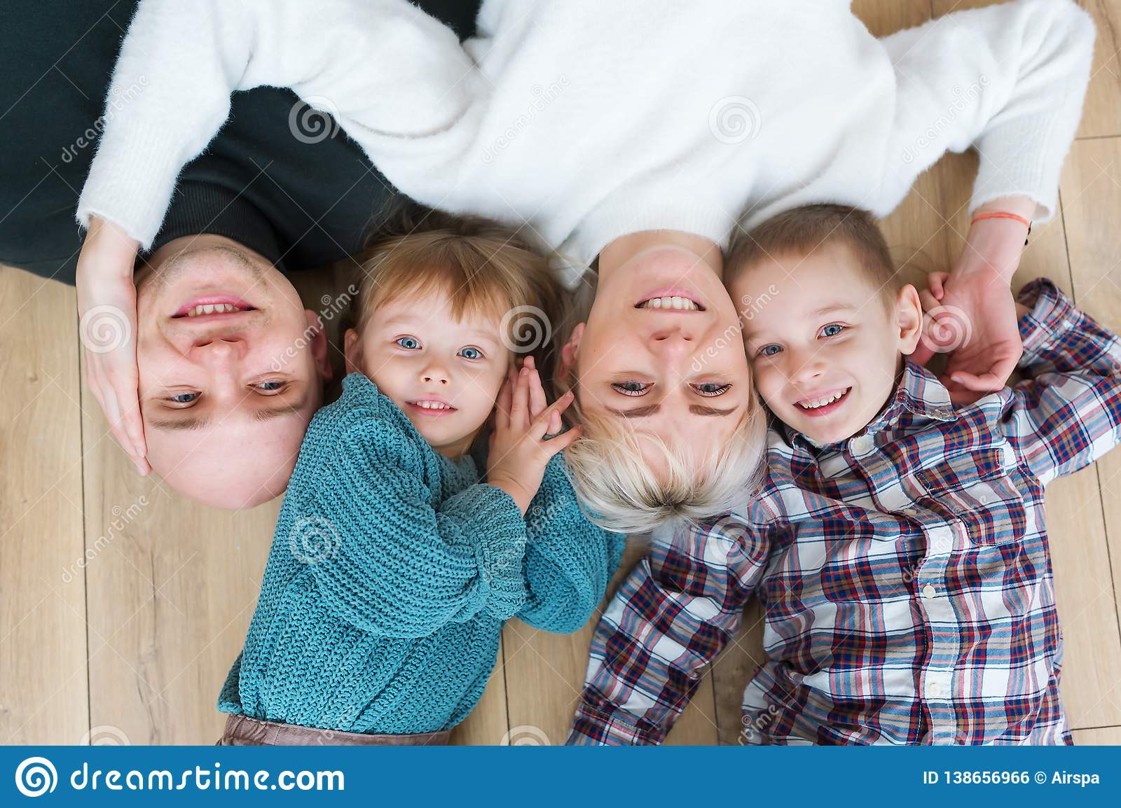 Top view of beautiful young parents, their cute little daughter and son looking at camera and smiling