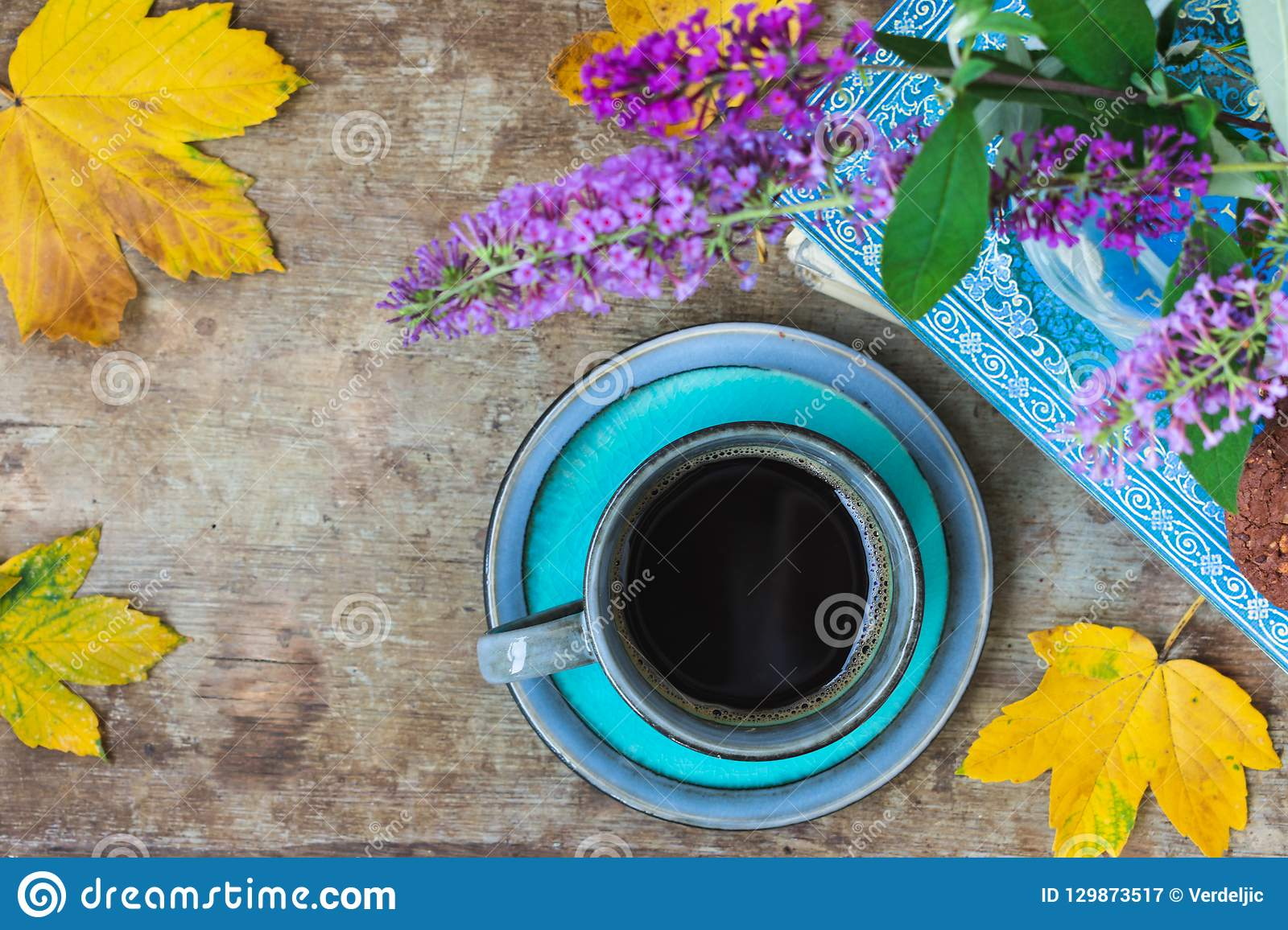 Top view of a blue cup of coffee, book, cookies, purple flowers in a vase and golden leaves on wooden background