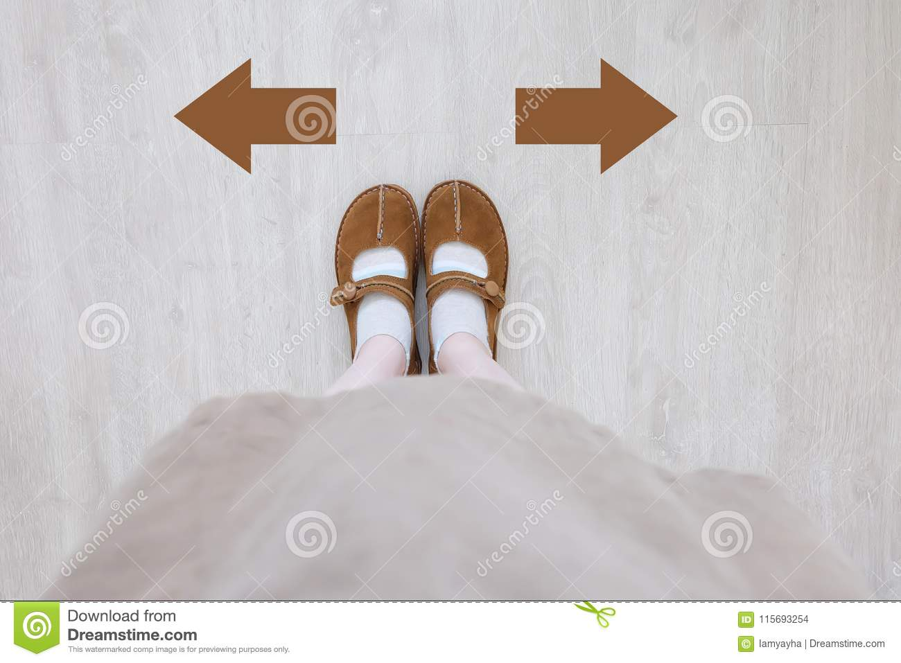 Top View of Brown Boot with Different Brown Decision Arrow. A Pair of Feet Standing. Shoes Walking Direction on Wooden