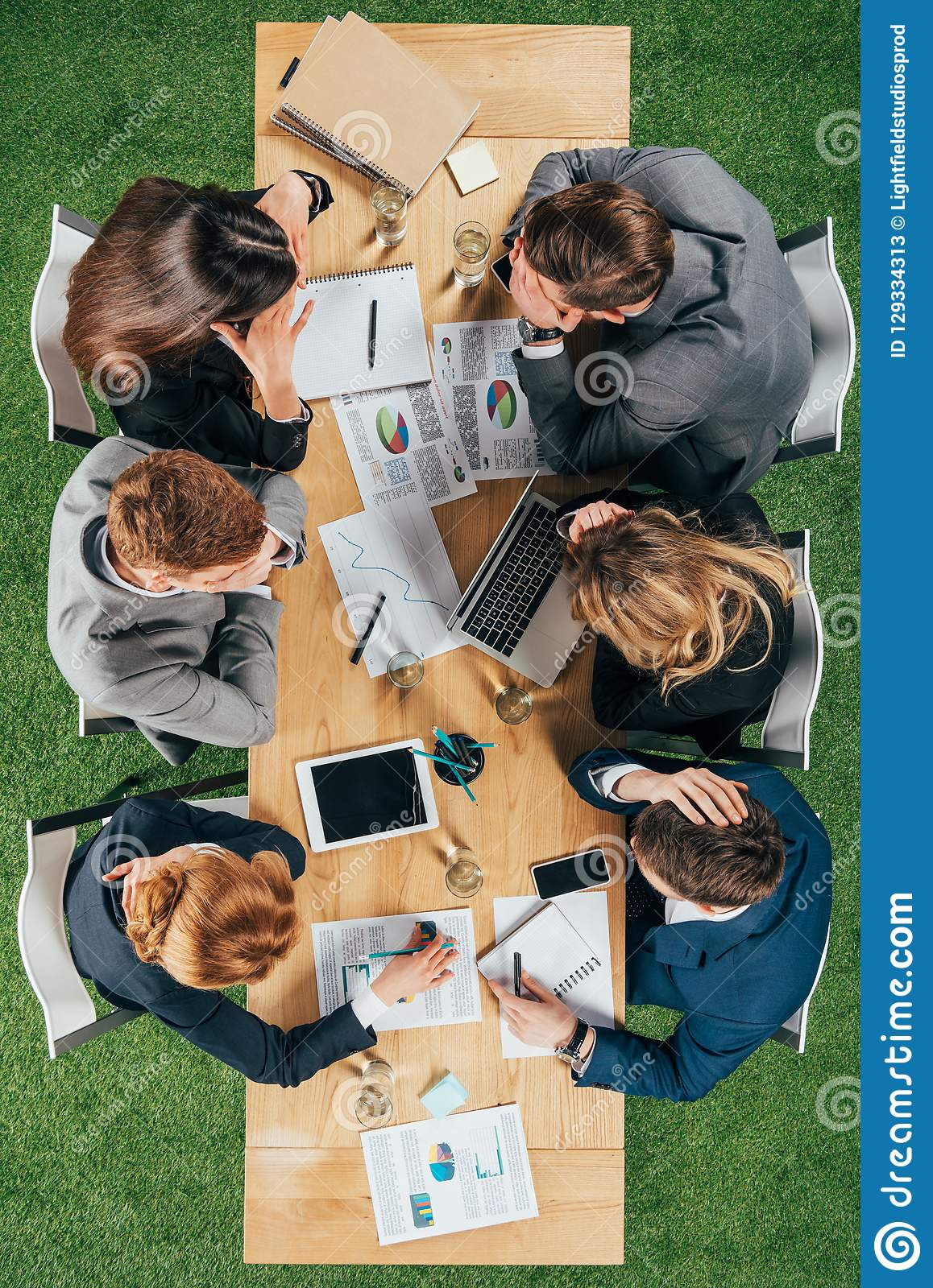 Top view of business partners having discussion at table with documents and devices